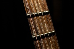 Acoustic guitar fretboard with rusty strings and dramatic light on a black background