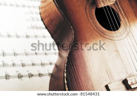 Acoustic guitar laying across sheet music