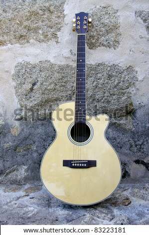 Acoustic guitar leaning against a stone wall with great colors