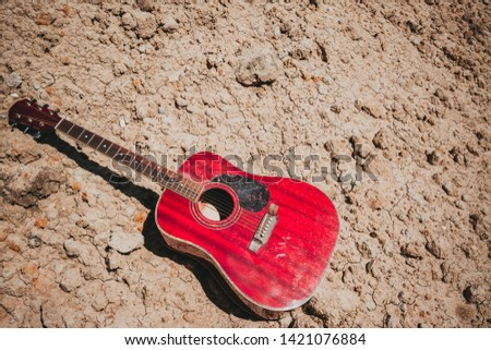 acoustic guitar lying on a desert land, vintage style with copy space