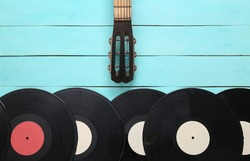 Acoustic guitar neck, vinyl record on blue wooden background. Musical concept. Minimalism. Top view. Flat lay