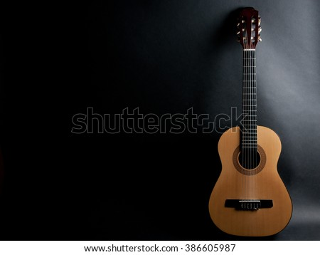 Acoustic guitar on a black background (with copy space)