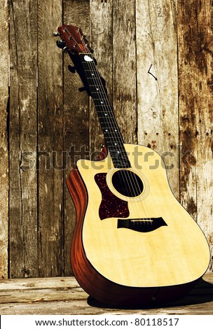 Acoustic guitar on a grunge wood backdrop in the sunshine with copy space.