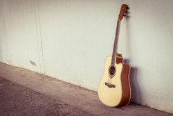 acoustic guitar on gray wall background with shadow edge.vintage tone.