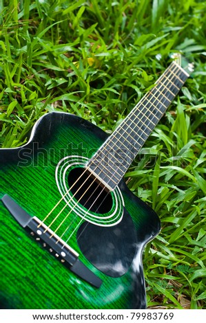 acoustic guitar on green grass yard