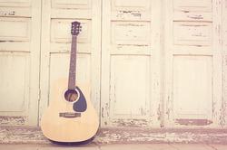 Acoustic guitar on old wooden door background