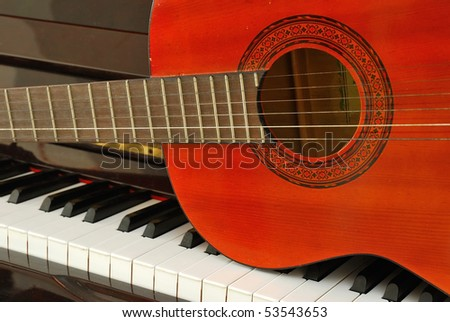 Acoustic guitar on piano keyboard. For concepts like music composition and creativity.
