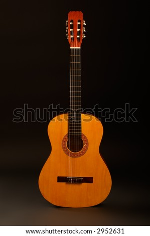Acoustic Guitar Over Black Background Standing Position