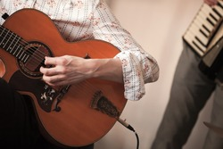 Acoustic guitar player, close-up photo with selective focus