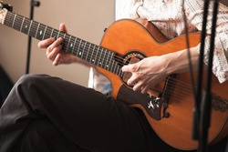 Acoustic guitar player, close-up photo with selective focus on hands