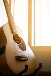 Acoustic guitar resting on guitar stand hanger with sun light from window, stylized as an old sepia photo