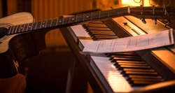 acoustic guitar stands on piano with notes, close-up, beautiful color background, music activity concept