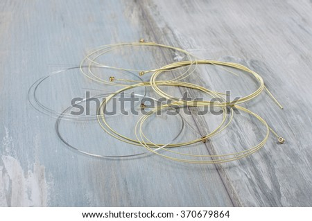 Acoustic guitar strings isolated on ancient wood background