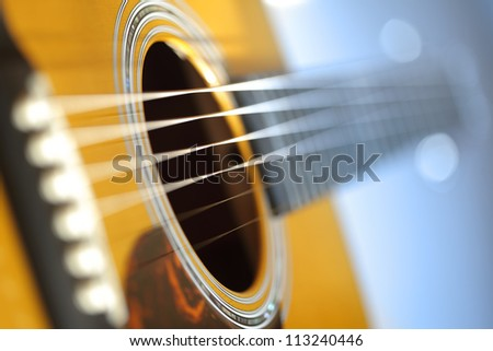 Acoustic guitar with very shallow depth of field, focus on strings above sound hole