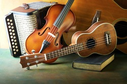 Acoustic musical instruments guitar ukulele violin and accordion still life style