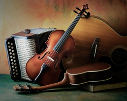 Acoustic musical instruments guitar ukulele violin and accordion with vintage book lay on fine painted floor and backdrop for wall web interior decoration still life style