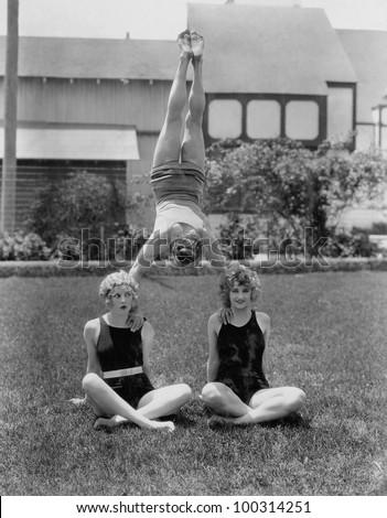Acrobat balancing on womens shoulders
