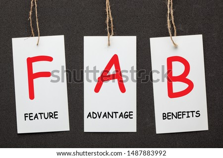 Acronym FAB - Feature Advantage Benefits written on paper labels set on black background. Business concept Сток-фото ©
