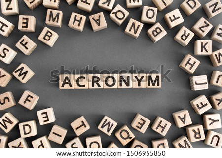 acronym - word from wooden blocks with letters, use of acronyms in the modern world abbreviation concept, random letters around, top view on wooden background Сток-фото ©