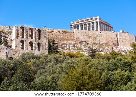 Acropolis hill and Parthenon temple in summer, Athens, Greece. Famous Acropolis is top landmark of Athens. Scenic view of Ancient Greek ruins in Athens center. Monument of historical Athens city.