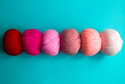 Acrylic balls of yarn on a blue background. A nuanced combination of colors. The skeins are grouped in one row.