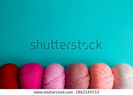 Acrylic balls of yarn on a blue background. A nuanced combination of colors. The skeins are located horizontally at the bottom. Photo stock ©