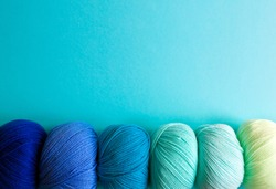 Acrylic balls of yarn on a blue background. Nuance color combination. The skeins are located horizontally at the bottom.