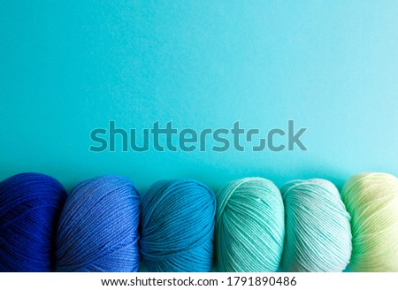 Acrylic balls of yarn on a blue background. Nuance color combination. The skeins are located horizontally at the bottom. Photo stock ©