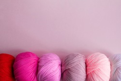 Acrylic balls of yarn on a pink background. A nuanced combination of colors. The skeins are located horizontally at the bottom.