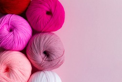 Acrylic balls of yarn on a pink background. Nuance color combination. Skeins are located vertically on the left.