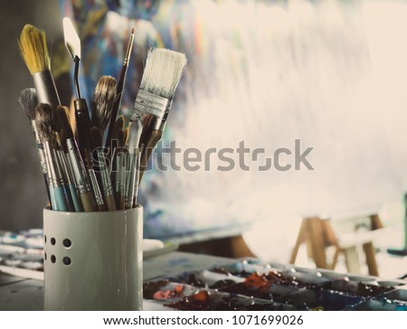 Acrylic Color in Palette, Brush, Wooden Figure,  Trowel on The Table and Canvas on the   easel in The Artist Studio #1071699026