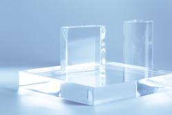 Acrylic empty podium for product presentation on neutral grey background, transparent geometric pedestals
