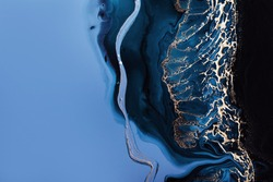 Acrylic Fluid Art. Dark blue waves in abstract ocean and golden foam. Marble effect background or texture.