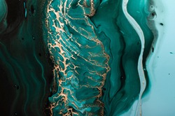 Acrylic Fluid Art. Dark green waves in abstract ocean and golden foamy waves. Marble effect background or texture.