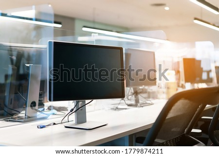 Acrylic plexiglass separator setting on the desk with monitor in the office. New normal Concept for social distancing in offices during the Covid-19 pandemic. Precaution and safe. Stockfoto ©