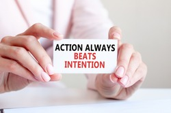 action always beats intention is written on a white business card in a woman's hands. Pink background. Business and advertising concept