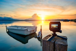Action camera on mini tripod over a wooden pier, taking video on the pond at sunset. Action camera shoots sunset panorama of the pond at sunset.