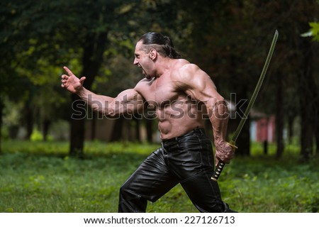 Action Hero Muscled Man Holding A Ancient Sword - Standing In Forest Wearing Leather Pants