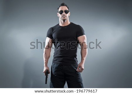 Action hero muscled man holding a gun. Wearing black t-shirt with pants and sunglasses. Studio shot against grey.