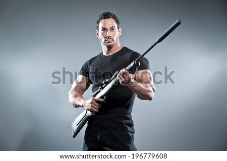 Action hero muscled man holding a rifle. Wearing black t-shirt and pants. Studio shot against grey.