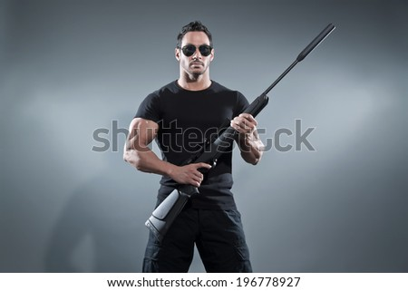 Action hero muscled man holding a rifle. Wearing black t-shirt with pants and sunglasses. Studio shot against grey.