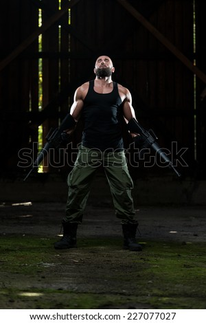 Action Hero Muscled Man Holding Machine Gun - Standing In Abandoned Building Wearing Green Pants