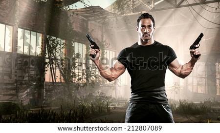 Action hero muscled man holding two guns. Standing in abandoned building. Wearing black t-shirt and pants.