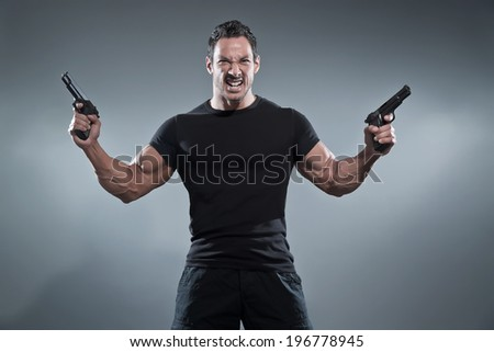 Action hero muscled man holding two guns. Wearing black t-shirt and pants. Studio shot against grey.