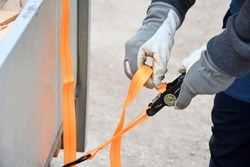 Action non focus fixing trailer strop or strap in orange nylon and metal, object helping for holding stuff , storage and transport for safty and security.