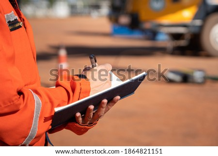 Action of safety officer is taking note on checklist with blurred background of crane truck vehicle. Safety inspection audit in heavy operation concept photo, selective focus at the person's hand.