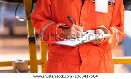 Action of safety officer is wirtinng and check on checklist document during safety audit and inspection at drilling site operation. Industrial expertise occupation photo.
