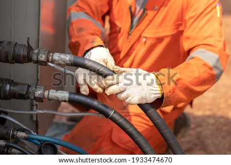 Action of worker hand is connecting and checking to high-pressure hydraulic hose line of power pack engine. Industrial working action photo, Close-up and selective focus.