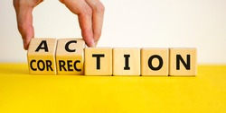 Action or correction symbol. Businessman turns wooden cubes and changes the word correction to action. Beautiful yellow table, white background, copy space. Business and action or correction concept.