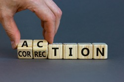 Action or correction symbol. Businessman turns wooden cubes and changes the word correction to action. Beautiful grey background, copy space. Business and action or correction concept.